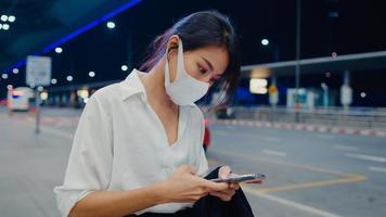 Asiatische Geschäftsmädchen kommen am Zielort an und tragen Gesichtsmaske. Geschäftspendler-Kovid-Pandemie, soziales Distanzierungskonzept für Geschäftsreisen. foto