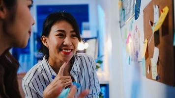 Gruppe junger asiatischer Geschäftsleute, die über Geschäfts-Brainstorming-Meeting diskutieren, die gemeinsam Daten austauschen und Whiteboard an der Wand mit Haftnotizen im Nachtbüro schreiben. Mitarbeiter-Teamwork-Konzept. foto