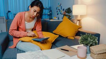 asiatische dame fühlen sich stress und sorgen sich um die rechnung und rechnung der kreditkarte, die das kredit auf dem sofa zu hause berechnet. Wohnungsbaudarlehensstress, Darlehen ohne Job, Coronavirus-Härtedarlehen, Darlehenszahlungskonzept nicht möglich. foto