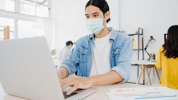 Asiatischer Geschäftsmann, der eine medizinische Gesichtsmaske für soziale Distanzierung in einer neuen normalen Situation zur Virusprävention trägt, während er den Laptop wieder bei der Arbeit im Büro verwendet. Lebensstil nach dem Corona-Virus. foto