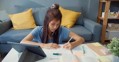 junge asiatische Mädchen Teenager mit Freizeitkleidung Kopfhörer verwenden digitale Tablette online lernen Vorlesungsnotizbuch im Wohnzimmer im Haus schreiben. Isolieren Sie das Online-E-Learning-Konzept für die Coronavirus-Pandemie. foto