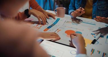 Millennial-Asien-Leute treffen Brainstorming-Ideen über neue Papierkram-Projektkollegen, die zusammenarbeiten, planen eine Erfolgsstrategie und genießen Teamarbeit in einem kleinen modernen Nachtbüro. Mitarbeiter-Teamwork-Konzept. foto