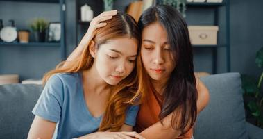 asiatische Teenager, die sich umarmen, um ihre traurigen besten Freunde davon zu beruhigen, sich von der Trennung von ihrem Freund im Wohnzimmer zu Hause niedergeschlagen zu fühlen. Freundschaftsberatung und Pflege, unglückliches Mädchen unterstützt ihre Freundin. foto