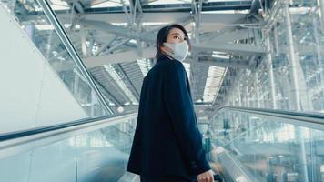 Asiatische Geschäftsmädchen tragen Gesichtsmaske ziehen Gepäckständer auf Rolltreppe Schauen Sie sich um, gehen Sie zum Terminal am internationalen Flughafen. Geschäftspendler-Kovid-Pandemie, soziales Distanzierungskonzept für Geschäftsreisen. foto