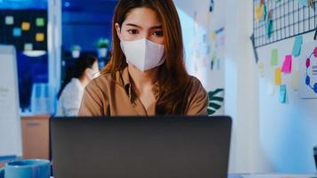 Fröhliche Geschäftsfrau in Asien, die eine medizinische Gesichtsmaske für soziale Distanzierung in einer neuen normalen Situation zur Virenprävention trägt, während sie in der Büronacht den Laptop bei der Arbeit verwendet. Leben und Arbeiten nach dem Coronavirus. foto