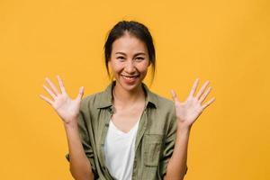 junge asiatische dame mit positivem ausdruck, breit lächeln, in legerer kleidung gekleidet und auf gelbem hintergrund in die kamera schauen. glückliche entzückende frohe frau freut sich über erfolg. Gesichtsausdruck Konzept. foto