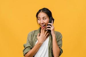 junge asiatische Dame telefoniert mit positivem Ausdruck, lächelt breit, in Freizeitkleidung gekleidet, fühlt sich glücklich und steht isoliert auf gelbem Hintergrund. glückliche entzückende frohe frau freut sich über erfolg. foto