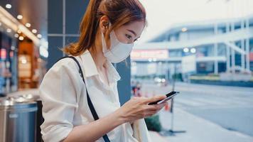 junge asiatische Geschäftsfrau in modischer Bürokleidung mit medizinischer Gesichtsmaske mit Smartphone, die Textnachrichten schreibt, während sie nachts in der urbanen modernen Stadt im Freien sitzt. Business-on-Go-Konzept. foto