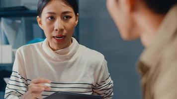 glückliche junge asiatische geschäftsleute und geschäftsfrauen, die sich treffen, um ein paar neue projektideen für seinen partner zu erarbeiten, der zusammenarbeitet, um eine erfolgsstrategie zu planen, genießen teamarbeit in einem kleinen modernen heimbüro. foto