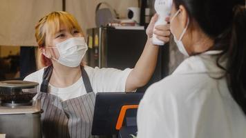 junge asiatische Restaurantmitarbeiterinnen, die vor dem Betreten eine schützende Gesichtsmaske mit einem Infrarot-Thermometer-Checker oder einer Temperaturpistole auf der Stirn des Kunden tragen. Lebensstil nach dem Corona-Virus neu normal. foto