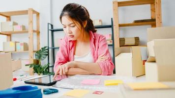 Junge asiatische Unternehmerin Geschäftsfrau Produktbestellung auf Lager prüfen und auf Tablet-Computer-Arbeit im Home-Office speichern. Kleinunternehmer, Online-Marktlieferung, Lifestyle-Freelance-Konzept. foto