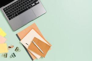 kreatives flaches Laienfoto des Arbeitsplatzschreibtisches. Schreibtisch von oben mit Laptop, Kaffeetasse und offenem schwarzen Notizbuch auf pastellgrünem Hintergrund. Draufsichtmodell mit Kopienraumfotografie. foto
