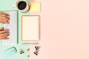 kreatives flaches Laienfoto des Arbeitsplatzschreibtisches. Schreibtisch von oben mit Tastatur, Maus und offenem Mockup-Schwarz-Notizbuch auf pastellgrünem rosafarbenem Hintergrund. Draufsichtmodell mit Kopienraumfotografie. foto
