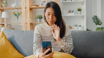 kranke junge asiatische frau hält medizin sitzen auf couch videoanruf mit telefon konsultieren sie mit arzt zu hause. Mädchen nehmen Medikamente nach ärztlicher Verordnung, Quarantäne zu Hause, soziales Distanzierungs-Coronavirus-Konzept. foto