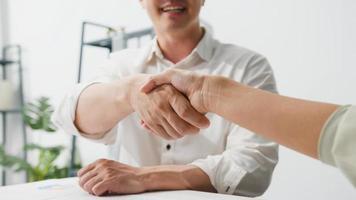 Gemischtrassige Gruppe junger kreativer Menschen in intelligenter Freizeitkleidung, die über Geschäfte diskutieren, die Hände schütteln und lächeln, während sie in einem modernen Büro sitzen. partnerkooperation, mitarbeiterteamwork-konzept. foto