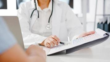 Junge asiatische Ärztin in weißer medizinischer Uniform mit Zwischenablage liefert großartige Nachrichtengespräche diskutieren Ergebnisse oder Symptome mit männlichen Patienten, die am Schreibtisch in einer Gesundheitsklinik oder einem Krankenhausbüro sitzen. foto