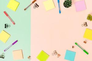minimaler arbeitsplatz - kreatives flaches foto des arbeitsplatzes. Schreibtisch von oben mit Haftnotiz auf pastellgrünem rosafarbenem Hintergrund. Draufsicht mit Kopienraum, Flachfotografie.