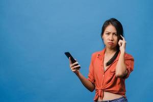 Denken träumende junge asiatische Dame mit Telefon mit positivem Ausdruck, gekleidet in Freizeitkleidung, die sich glücklich fühlt und isoliert auf blauem Hintergrund steht. glückliche entzückende frohe frau freut sich über erfolg. foto