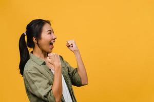 junge asiatische dame mit positivem ausdruck, fröhlich und aufregend, gekleidet in lässiges tuch auf gelbem hintergrund mit leerem raum. glückliche entzückende frohe frau freut sich über erfolg. Gesichtsausdruck Konzept. foto