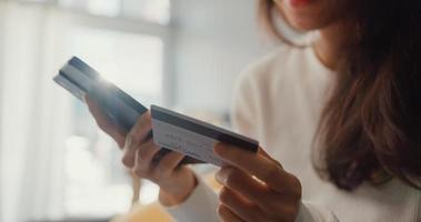 Nahaufnahme der jungen asiatischen Dame, die das Online-Shopping-Produkt für die Handybestellung verwendet und die Rechnung mit Kreditkarte bezahlt, sitzt auf der Couch im Wohnzimmer im Haus, Quarantäneaktivität, lustige Aktivität zur Vorbeugung von Coronaviren. foto