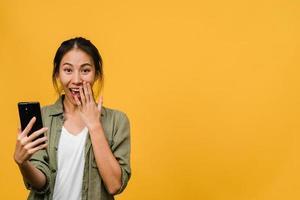 überraschte junge asiatische dame mit handy mit positivem ausdruck, lächelt breit, in legerer kleidung gekleidet und steht einzeln auf gelbem hintergrund. glückliche entzückende frohe frau freut sich über erfolg. foto