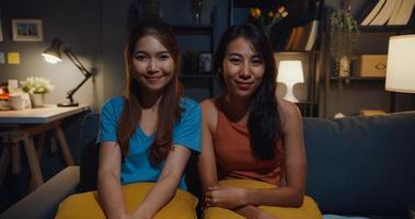 Teenager-Asien-Frauen, die sich glücklich lächeln und auf die Kamera schauen, während sie sich zu Hause im Wohnzimmer entspannen. fröhliche Mitbewohnerinnen Videoanruf mit Freund und Familie, Lifestyle-Frau zu Hause Konzept. foto