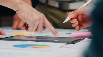 Millennial Asia Geschäftsleute und Geschäftsfrauen treffen Brainstorming-Ideen über neue Papierkram-Projektkollegen, die zusammenarbeiten und Erfolgsstrategien planen, genießen Teamarbeit in einem kleinen modernen Nachtbüro. foto