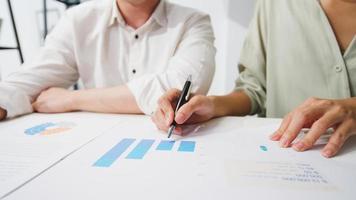 glückliche junge asiatische geschäftsleute und geschäftsfrauen, die brainstorming-ideen über neue papierkram-projektkollegen treffen, die zusammenarbeiten und erfolgsstrategien planen, genießen teamarbeit in einem kleinen modernen büro. foto