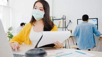 Asiatische Geschäftsfrau, die eine medizinische Gesichtsmaske für soziale Distanzierung in einer neuen normalen Situation zur Virusprävention trägt, während sie den Laptop wieder bei der Arbeit im Büro verwendet. Lebensstil nach dem Corona-Virus. foto