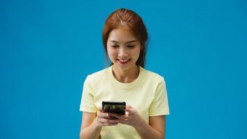 junge asiatische dame, die telefon mit positivem ausdruck verwendet, breit lächelt, in lässiger kleidung gekleidet, glücklich fühlt und isoliert auf blauem hintergrund steht. glückliche entzückende frohe frau freut sich über erfolg. foto