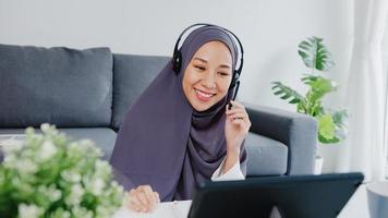 asiatische muslimische dame tragen kopfhörer mit tablet sprechen mit kollegen über verkaufsbericht in konferenz-videoanrufen, während sie von zu hause im wohnzimmer arbeiten. soziale Distanzierung, Quarantäne wegen Corona-Virus. foto