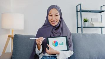 asiatische muslimische dame tragen hijab verwenden computer-laptop sprechen mit kollegen über verkaufsbericht in videoanrufbesprechung, während sie von zu hause aus im wohnzimmer arbeiten. soziale Distanzierung, Quarantäne wegen Corona-Virus. foto