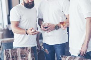 Fröhliche alte Freunde kommunizieren miteinander und telefonieren, mit Gläsern Whisky oder Wein in der Kneipe. Konzept der Unterhaltung und des Lebensstils. Wifi-verbundene Leute in Stehtischtreffen foto