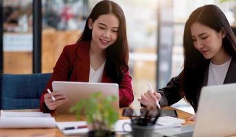 Teammeeting.Gruppe von zwei Geschäftsleuten, die mit einem neuen Startup-Projekt im modernen Büro arbeiten.Touch-Pad in Frauenhänden foto