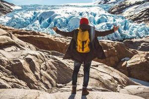 Reisender Mann, der auf einem Felsen auf dem Hintergrund eines Gletschers, der Berge und des Schnees steht foto