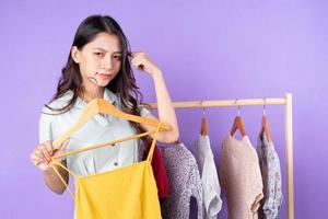 Bild einer Modefrau im Rock, die in der Nähe des Kleiderschranks mit Kleidung steht und auswählt, was sie einzeln auf violettem Hintergrund tragen soll foto