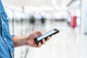 Mannhand, die mobiles Smartphone mit leerem Bildschirm auf unscharfem Hintergrund des Einkaufszentrums hält. foto