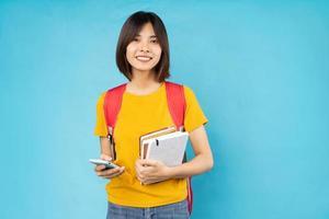 Porträt der jungen Studentin, isoliert auf blauem Hintergrund foto