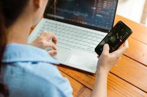 Frauenhand mit Telefon und Laptop bei der Überprüfung der Börse foto