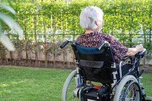 asiatische ältere Patientin auf elektronischem Rollstuhl im Park. foto
