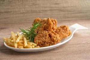Brathähnchen und Kartoffelchips mit Rosmarinblatt, kalorienreiches Junkfood auf weißem Teller serviert foto