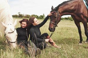 zwei junge schöne mädchen in ausrüstung zum reiten in der nähe ihrer pferde. sie lieben tiere foto