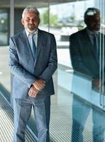 Senior Geschäftsmann mit verschränkten Armen außerhalb des modernen Bürogebäudes. foto