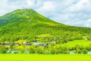 Türkisfarbenes Schmelzwasser fließt in einem Fluss durch das Dorf in Norwegen. foto