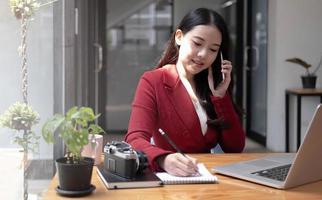 junge Frau, die am Handy spricht und Notizen schreibt, während sie an ihrem Schreibtisch sitzt. Asiatin, die im Homeoffice arbeitet foto