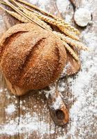 Brot mit Weizenähren und Mehl foto