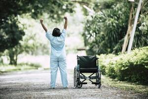 Physiotherapie ältere Frau mit Rollstuhl im Park foto