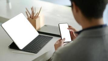 junger Geschäftsmann hält ein Smartphone mit leerem Bildschirm in der Hand und einen Laptop mit leerem Bildschirm auf dem Schreibtisch. foto