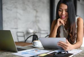 weibliche Geschäftsleute benutzen das Tablet in der Freizeit. sie lächelt glücklich. Grafiken, auf den Tisch gelegte Dokumente. foto