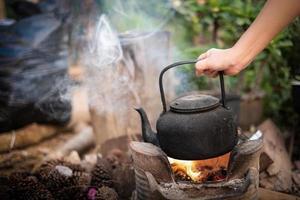 Nahaufnahme Hand, die alten Wasserkocher auf dem Feuer mit einem Holzkohleofen auf unscharfem Hintergrund hält foto